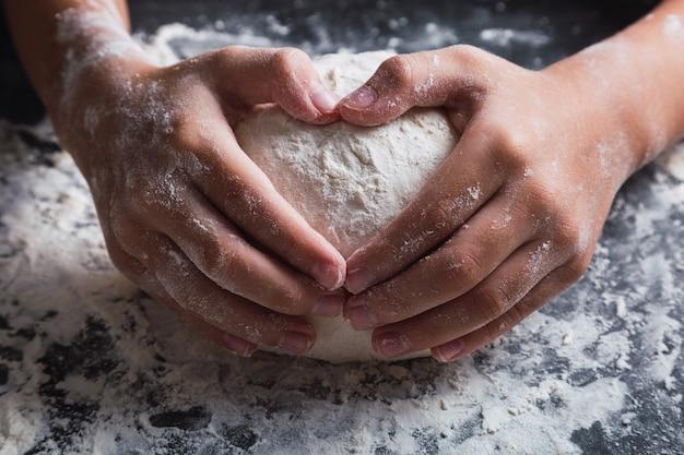 Gros plan des mains dans la pâte, faisant un coeur.