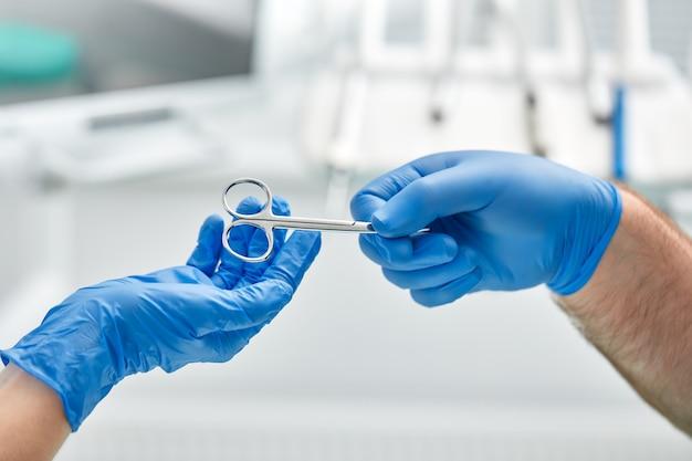 Gros plan des mains d'un dentiste et d'une infirmière chirurgienne sur une salle d'opération lors d'une opération d'implant dentaire