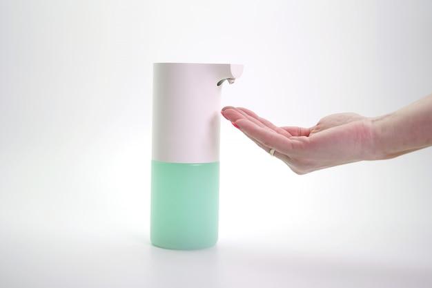 Gros plan des mains désinfectées avec un distributeur automatique de mousse, mur isolé. protection contre les virus et les bactéries