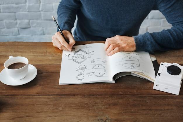Gros plan des mains, dessin des bannières badges en dessinant le livre sur la table en bois