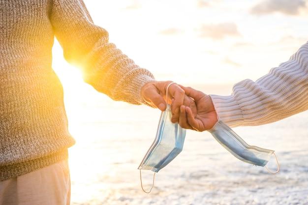 Gros plan sur les mains de deux personnes se tenant avec leur masque pour se protéger du covid ou du virus dans les mains après avoir gagné contre le coronavirus et être libre à l'extérieur à la plage