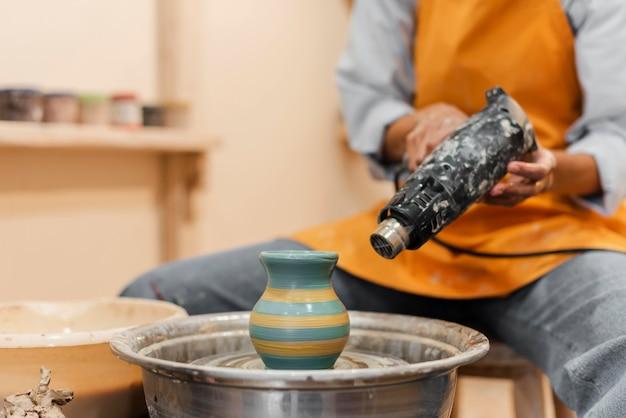 Gros plan des mains avec dispositif de poterie