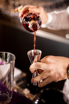 Gros plan des mains du barman versant une boisson alcoolisée. fabrication de boissons professionnelles