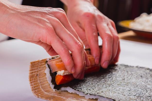 Gros plan des mains du chef faisant des sushis.