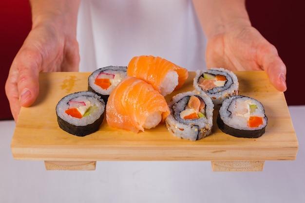 Gros plan sur les mains du chef tenant une planche en bois de délicieux sushis.