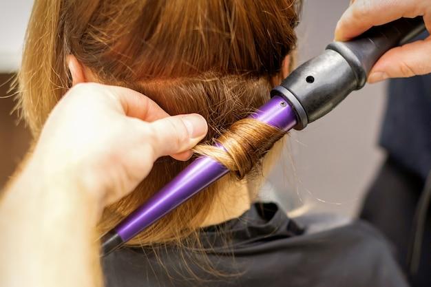Gros plan des mains du coiffeur à l'aide d'un fer à friser pour les boucles de cheveux dans un salon de beauté.