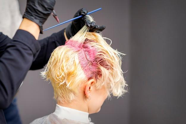 Gros plan des mains du coiffeur appliquant un colorant rose sur les cheveux blonds de la femme dans un salon de coiffure