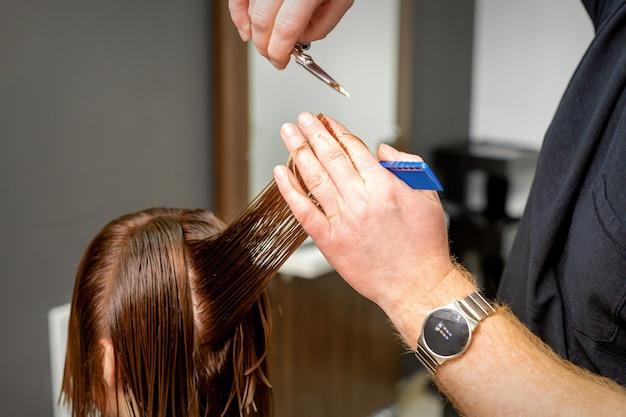 Gros plan des mains du coiffeur masculin coupe les cheveux des femmes dans un salon de coiffure