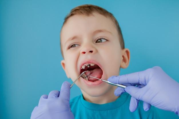 Gros plan des mains du dentiste avec un assistant en gants bleus traitent les dents d'un enfant, le visage du patient est fermé