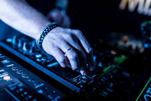 Gros plan des mains du dj contrôlant une table de musique dans une boîte de nuit.