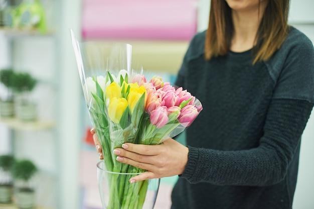 Gros plan des mains du fleuriste avec des fleurs. fleuriste, tenue, fleurir, bouquet, rose, tulipes