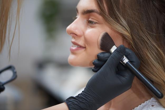 Gros plan des mains du maquilleur contour du visage du client dans un salon de beauté