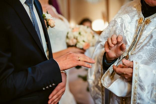 Gros plan des mains du marié et du prêtre dans une église