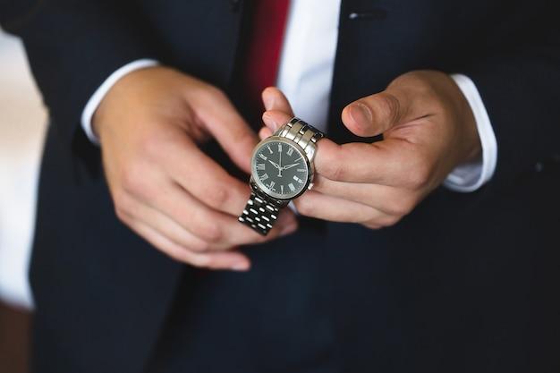 Gros plan des mains du marié avec une horloge