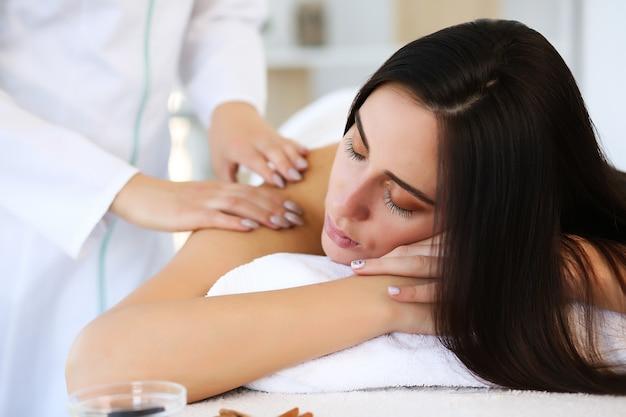 Gros plan des mains du masseur massant le dos d'un client