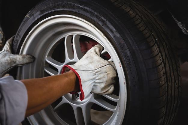 Gros plan sur les mains du mécanicien de réparation pendant l'entretien et le changement de pneu d'une voiture
