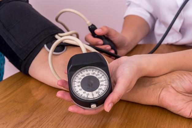 Gros plan des mains du médecin et du patient avec tonomètre