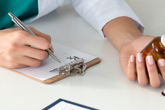 Gros plan des mains du médecin écrivant la prescription et tenant la bouteille avec des pilules. concept de soins de santé, médical et pharmacie.