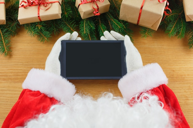 Gros plan des mains du père noël sur une tablette numérique vierge