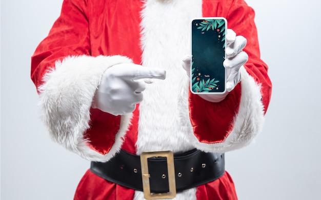 Gros plan sur les mains du père noël tenant un appareil avec un design élégant sur l'écran, fond. concept de soldes d'hiver, nouvel an 2021 et célébration de noël, appareil et gadgets modernes, achats en ligne.