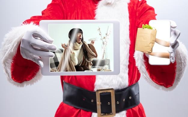 Gros plan sur les mains du père noël tenant le dispositif avec les mains donnant de la nourriture à une femme malade sur l'écran. concept de livraison, nouvel an 2021 et célébration de noël, appareil et gadgets, achats en ligne.