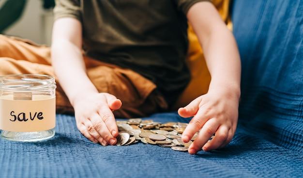 Gros plan sur les mains du petit garçon enfant saisissant et mettant des pièces de pile dans un bocal en verre avec sauvegarde