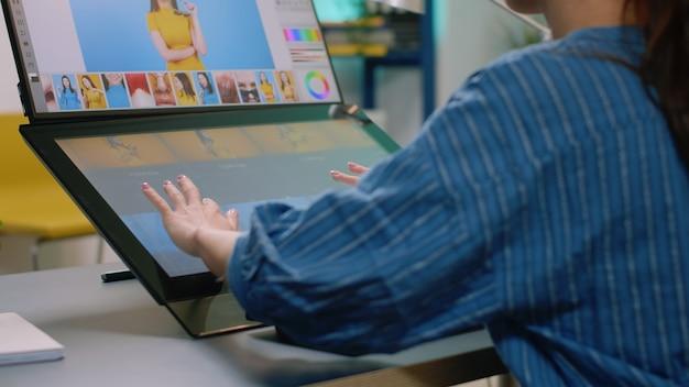 Gros plan des mains du photographe à l'aide d'un moniteur à écran tactile