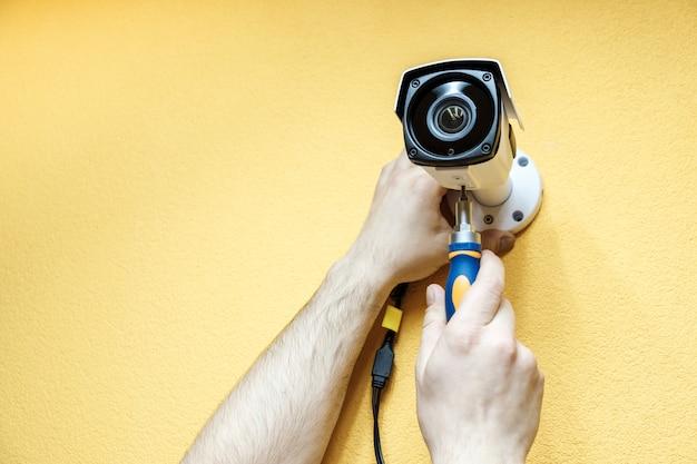 Gros plan des mains du technicien ajustant la caméra cctv