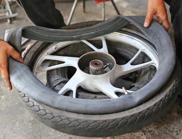 Gros plan des mains du technicien en fixant la roue de la moto