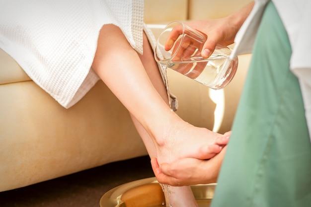 Gros plan des mains du thérapeute masculin laver les jambes d'une jeune femme dans un salon de beauté spa