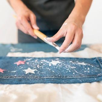 Gros plan mains éclaboussures de jeans