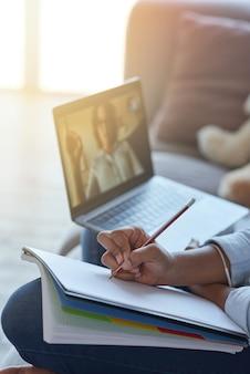 Gros plan sur les mains d'une écolière adolescente prenant des notes tout en ayant une leçon en ligne avec un enseignant via