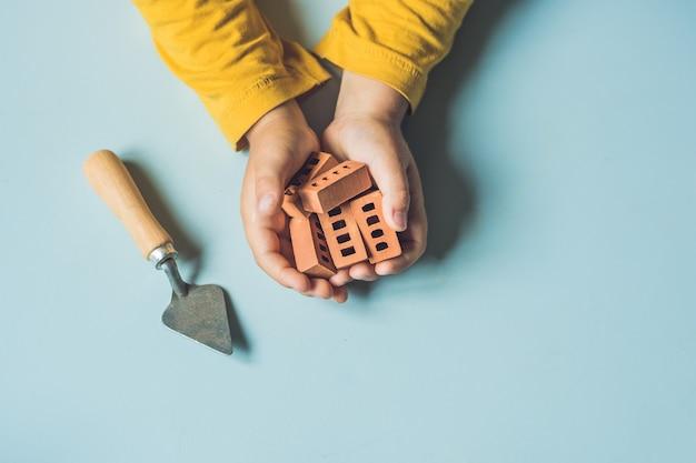 Gros plan des mains de l'enfant jouant avec de vraies petites briques d'argile à la table