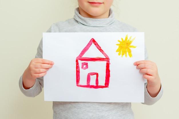 Gros plan des mains de l'enfant tenant la photo de la maison rouge avec le soleil couvrant son visage sur fond jaune. l'enfant apprend à dessiner.