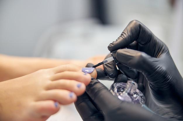 Gros plan des mains de l'esthéticienne dans des gants en latex pendant qu'elle peint les ongles des orteils de femme