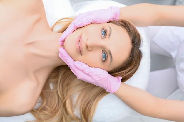 Gros plan des mains esthéticienne dans des gants touchant le visage de la jeune femme. concept de chirurgie plastique. beauté du visage. portrait de la belle femme blonde heureuse souriante avec un maquillage parfait et une peau douce et lisse.