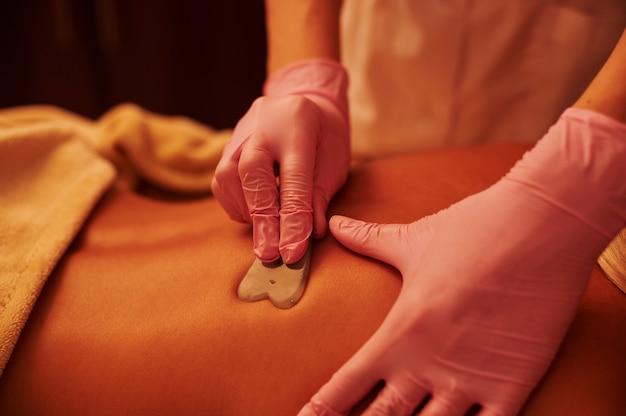 Gros plan des mains de l'esthéticienne faisant le massage gua sha