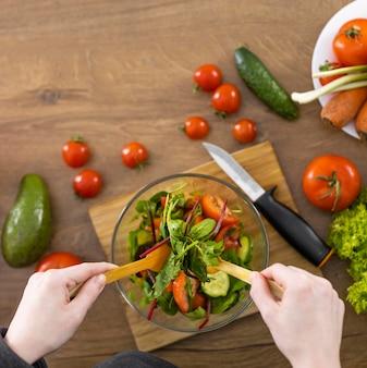 Gros plan des mains faisant la salade