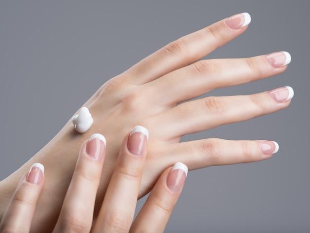 Gros plan des mains féminines appliquant la crème pour les mains