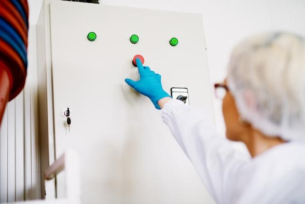 Gros plan des mains féminines en appuyant sur un bouton de démarrage sur le panneau de commande.