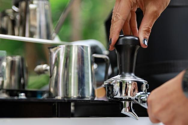 Gros plan des mains féminines. le barista prépare du café.