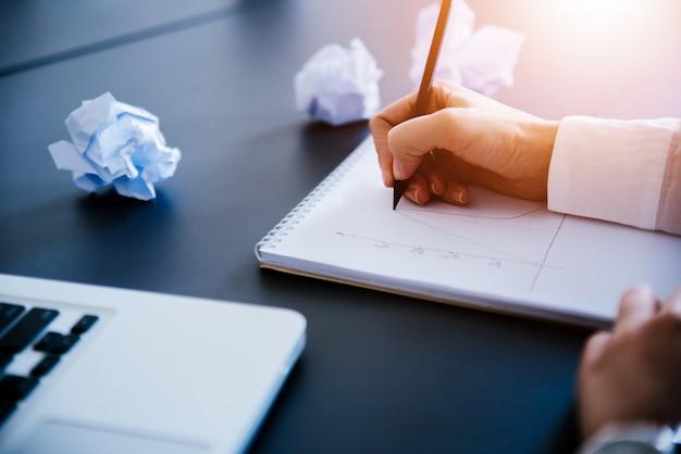Gros plan des mains féminines avec carnet, crayon et bourres de papier à l'étroit sur la table.