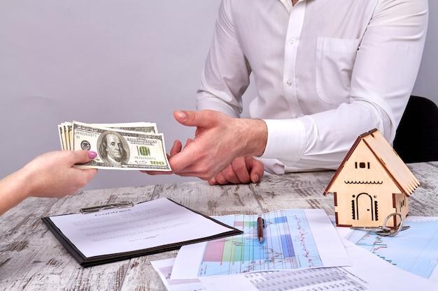 Gros plan des mains féminines donnant de l'argent en espèces à un agent immobilier