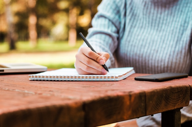 Gros plan de mains féminines écrivant sur un cahier vierge dans le parc.