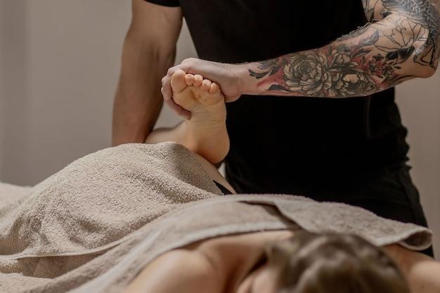 Gros plan des mains féminines faisant le massage des pieds. femme bénéficiant de massage des pieds de réflexologie dans un spa de bien-être.