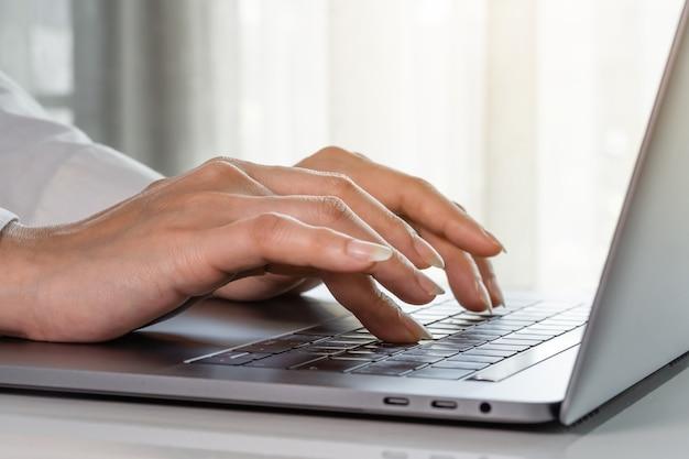 Gros plan des mains féminines de femme d'affaires en tapant sur un clavier d'ordinateur portable