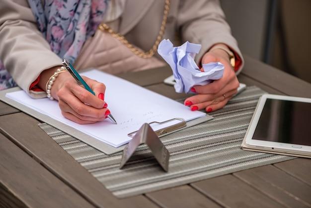 Gros plan, de, mains féminines femme écrivant quelque chose assis au café. signature de documents. l'autre main fend un morceau de papier.