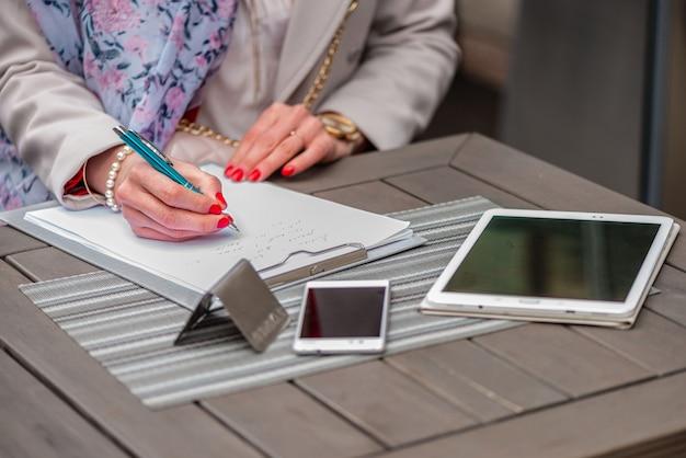 Gros plan, de, mains féminines femme écrivant quelque chose assis au café. signature de documents.