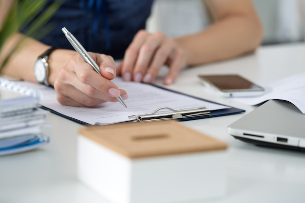 Gros plan des mains féminines. femme écrivant quelque chose assis à son bureau