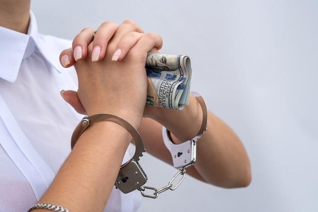 Gros plan des mains féminines menottes aux poignets et tenir les billets en dollars isolés sur fond gris. concept de corruption et de pot-de-vin
